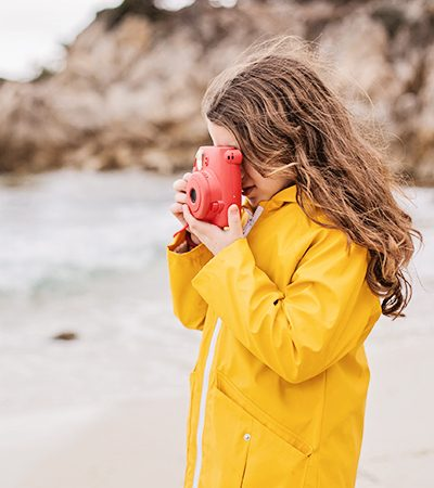 Side view of a young girl photographing on the beach.